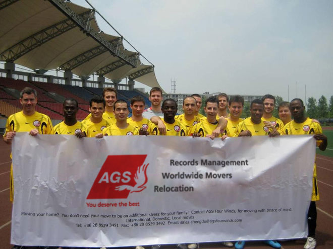 Football team holding a AGS Mover banner