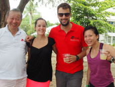 2 men and 2 women smiling and drinking during a petanque tournament