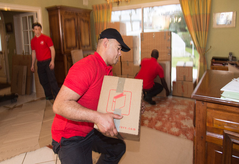 A packer from AGS Movers in Cape Town busy lifting a box