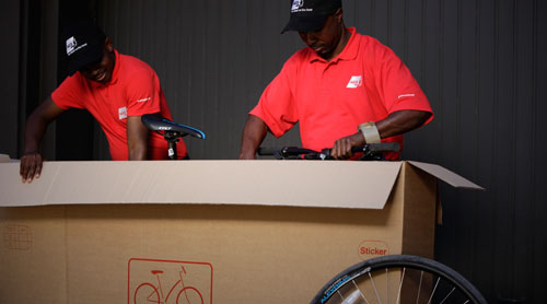 Professional movers packing bicycle in a customised carton