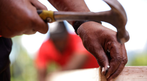 professional packer closing a wooden crate with a hammer and a nail
