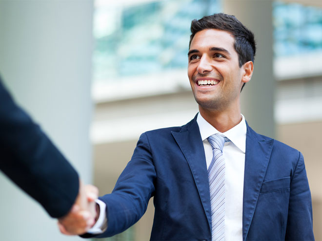 Man wearing a suit smiling and handshaking