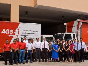 AGS Singapore staff posing in front of their facilities with trucks