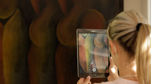 Woman taking a picture of a painting with a tablet